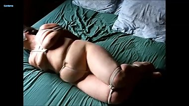 Ghis struggling in nude hogtied with crotchrope on bed.
